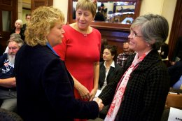 Republican Cathy Manchester (left) and Democrat Catherine Breen (right) shake hands while former lawmaker Meredith Strang Burgess smiles at them before a committee hearing on the Senate District 25 ballot issue on Tuesday at the State House in Augusta. Troy R. Bennett | BDN